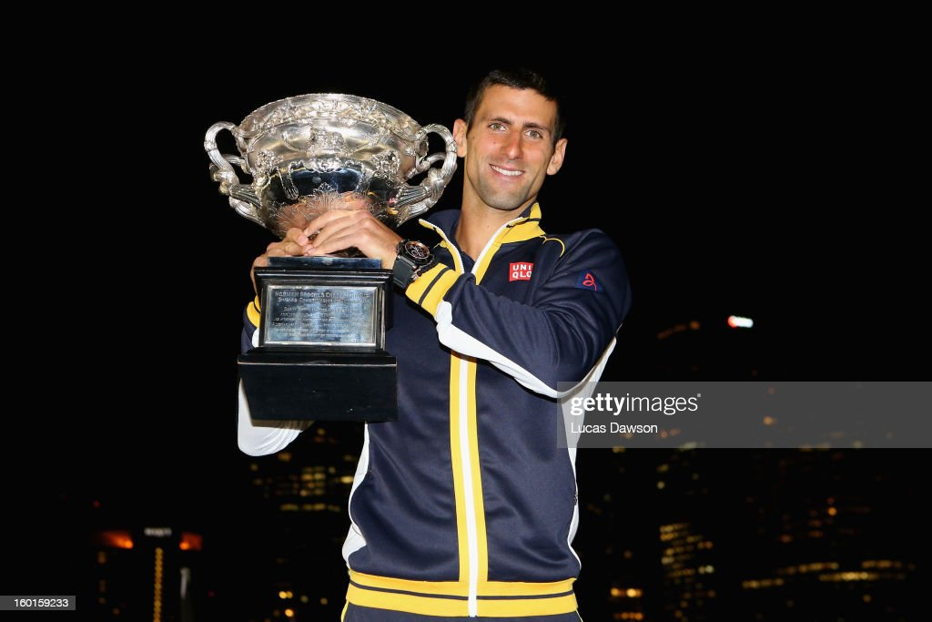 Novak Djokovic of Serbia poses with the Norman Brookes Challenge Cup in the early hours of January 28, 2013 after winning his men's final match against Andy Murray of Great Britain during day fourteen of the 2013 Australian Open at Melbourne Park on January 27, 2013 in Melbourne, Australia.