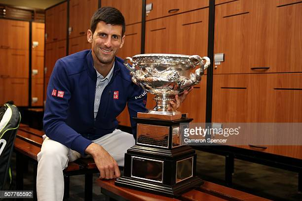 Novak Djokovic of Serbia poses with the Norman Brookes Challenge Cup in the players change rooms after winning the Men's Singles Final against Andy...