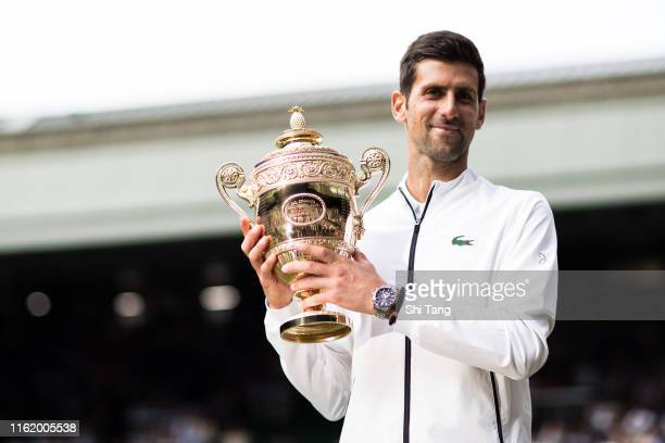 Novak Djokovic of Serbia poses with the trophy after winning the Men's Singles final against Roger Federer of Switzerland during Day thirteen of The...