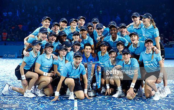 Novak Djokovic of Serbia poses with the trophy and ballboys following his victory during the men's singles final against Roger Federer of Switzerland...