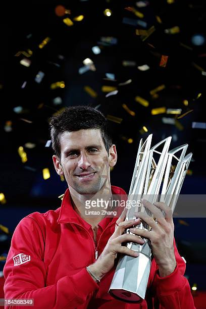 Novak Djokovic of Serbia poses with the winner's trophy after defeating Juan Martin Del Potro of Argentina during day seven of the Shanghai Rolex...