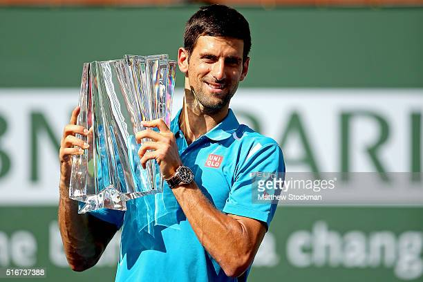 Novak Djokovic of Serbia poses with the winner's trophy after defeating Milos Raonic of Canada during the mens final of the BNP Paribas Open at the...