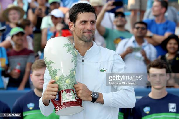 Novak Djokovic of Serbia poses with the winner's trophy after defeating Roger Federer of Switzerland during the men's final of the Western Southern...