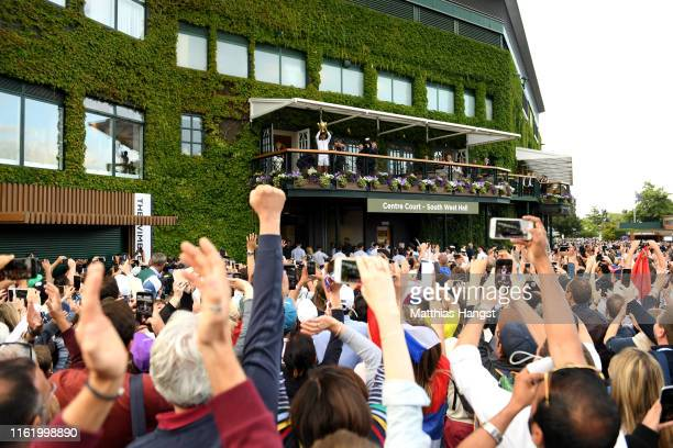 Novak Djokovic of Serbia presents the trophy to spectators from the clubhouse balcony after winning his Men's Singles final against Roger Federer of...