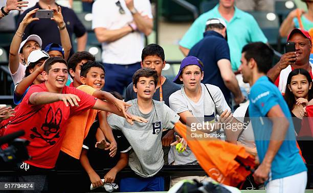 Novak Djokovic of Serbia pretends to throw the chair umbrella to the fans after his straight sets victory against Joao Sousa of Portugal in their...