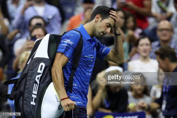 Novak Djokovic of Serbia reacts as he walks off court after retiring due to a shoulder injury during his Men's Singles fourth round match against...
