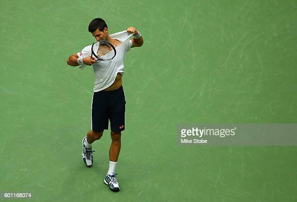 Novak Djokovic of Serbia reacts by ripping off his shirt while playing against Gael Monfils of France during their Men's Singles Semifinal Match on...