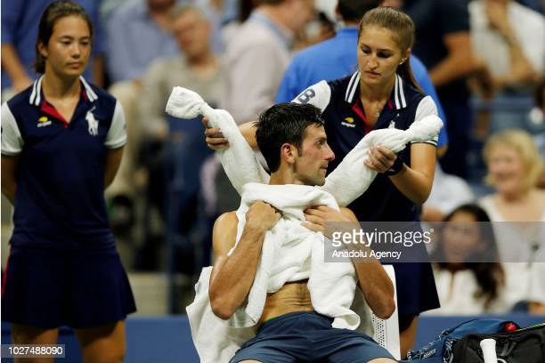 Novak Djokovic of Serbia reacts during break in play in his men's singles quarterfinal match against John Millman of Australia at the 2018 US Open in...