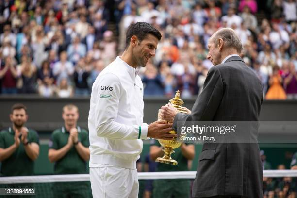 Novak Djokovic of Serbia receives the Men's Trophy from Prince Edward, Duke of Kent after the Men's Singles Final at The Wimbledon Lawn Tennis...