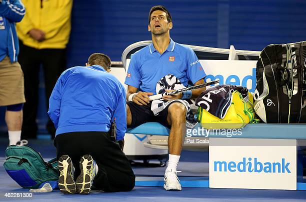 Novak Djokovic of Serbia receives treatment for a grazed knuckle during his match against Gilles Muller of Luxembourg on Rod Laver Arena during day...