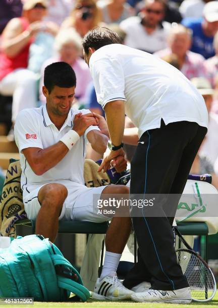 Novak Djokovic of Serbia recieves treatment for a shoulder injury during his Gentlemen's Singles third round match against Gilles Simon of France on...