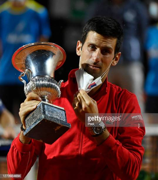 Novak Djokovic of Serbia removes his face mask as he celebrates with trophy after winning his men's final match against Diego Schwartzman of...