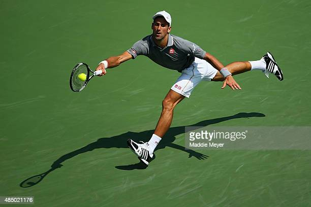 Novak Djokovic of Serbia returns a forehand to Roger Federer of Switzerland during the final round on Day 9 of the Western Southern Open at the...