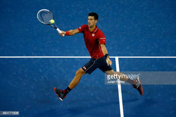 Novak Djokovic of Serbia returns a shot against Diego Schwartzman of Argentina during their men's singles first round match on Day One of the 2014 US...