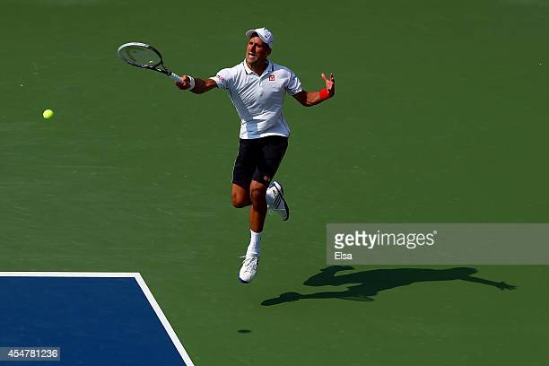 Novak Djokovic of Serbia returns a shot against Kei Nishikori of Japan during their men's singles semifinal match on Day Thirteen of the 2014 US Open...