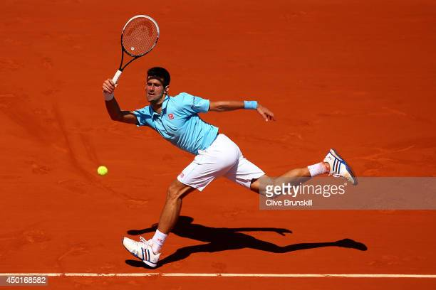 Novak Djokovic of Serbia returns a shot during his men's singles semifinal match against Ernests Gulbis of Latvia on day thirteen of the French Open...
