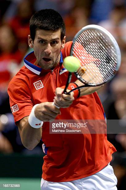 Novak Djokovic of Serbia returns a shot to John Isner during the first match of the Davis Cup tie between the United States and Serbia at Taco Bell...