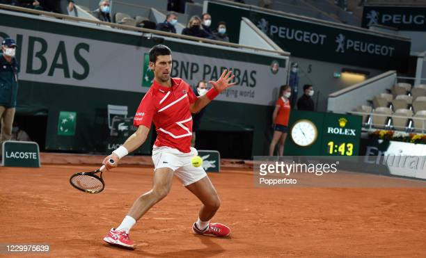 Novak Djokovic of Serbia returns the ball against Rafael Nadal of Spain during the men's singles final on day fifteen of the 2020 French Open at...