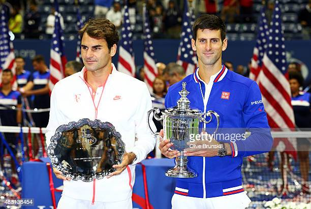 Novak Djokovic of Serbia right and Roger Federer of Switzerland celebrate with their trophies after their Men's Singles Final match on Day Fourteen...