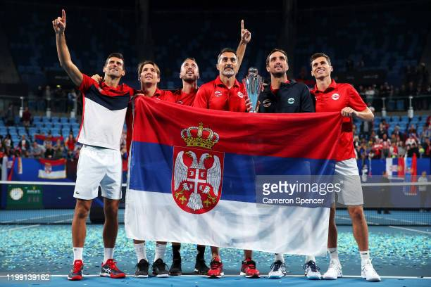 Novak Djokovic of Serbia Serbia captain Nenad Zimonjic pose with their flag on court after winning the ATP Cup final against Spain during day 10 of...