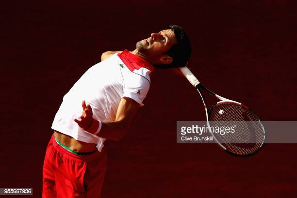 Novak Djokovic of Serbia serves against Kei Nishikori of Japan in their first round match during day three of the Mutua Madrid Open tennis tournament...