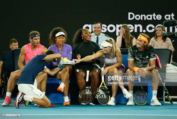 Novak Djokovic of Serbia serves drinks to Serena Williams of the USA during the Rally for Relief Bushfire Appeal event at Rod Laver Arena on January...