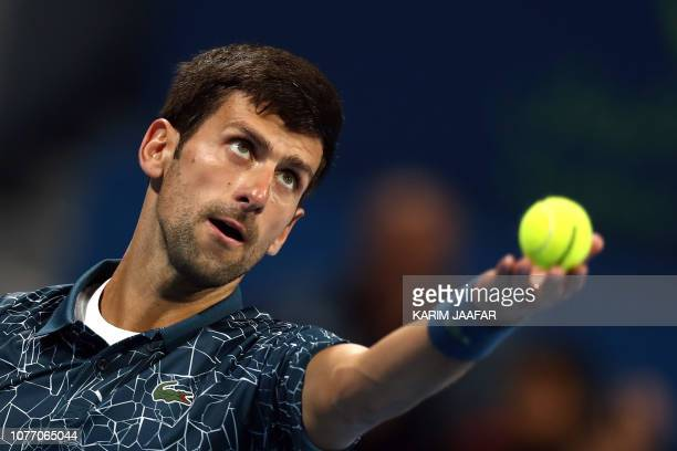 TOPSHOT Novak Djokovic of Serbia serves the ball to Roberto Bautista Agut of Spain during their ATP Qatar Open tennis semifinal match in Doha on...