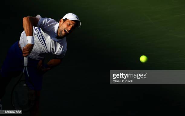 Novak Djokovic of Serbia serves while playing with Fabio Fognini of Italy against Lukasz Kubot of Poland and Marcelo Melo of Brazil during their...