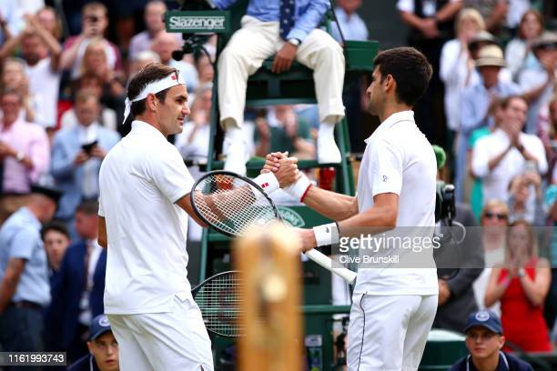 Novak Djokovic of Serbia shakes hands at the net with Roger Federer of Switzerland following victory in his Men's Singles final during Day thirteen...