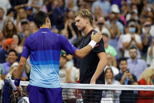 Novak Djokovic of Serbia shakes hands with Jenson Brooksby of the United States at center court after Djokovic won during their Men's Singles round...