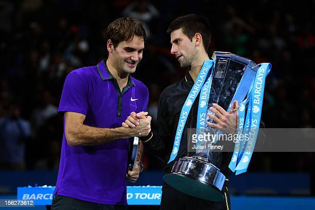 Novak Djokovic of Serbia shakes hands with Roger Federer of Switzerland as he holds the trophy following their men's singles final match against...