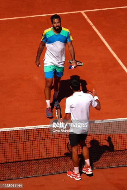 Novak Djokovic of Serbia shakes hands with Salvatore Caruso of Italy following victory in their mens singles third round match during Day seven of...