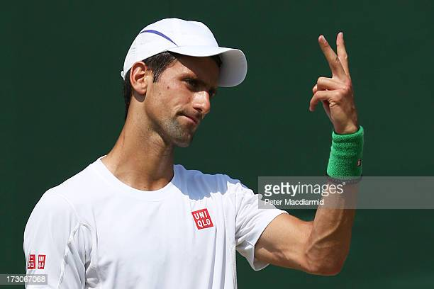Novak Djokovic of Serbia signals for more tennis balls during a practice session on day twelve of the Wimbledon Lawn Tennis Championships at the All...