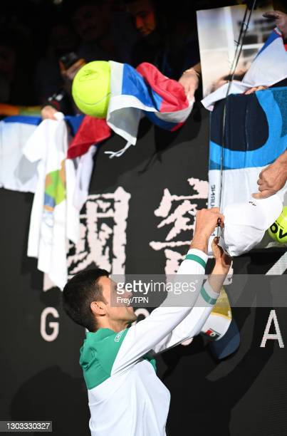 Novak Djokovic of Serbia signs autographs after beating Daniil Medvedev of Russia in the men's singles final during day 14 of the 2021 Australian...
