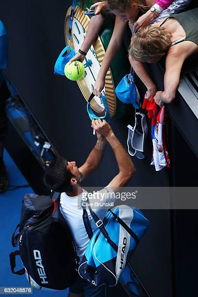 Novak Djokovic of Serbia signs autographs for fans after losing his second round match against Denis Istomin of Uzbekistan on day four of the 2017...