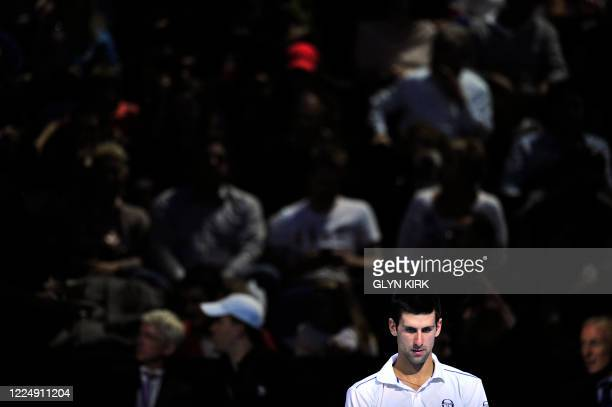 Novak Djokovic of Serbia sits in the break between games against Janko Tipsarevic of Serbia during their group A singles match in the round robin...