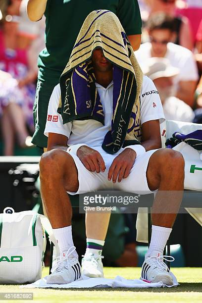 Novak Djokovic of Serbia sits with a towel on his head during his Gentlemen's Singles semifinal match against Grigor Dimitrov of Bulgaria on day...