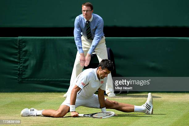 Novak Djokovic of Serbia slips on the grass after sliding to reach a shot during the Gentlemen's Singles semifinal match against Juan Martin Del...