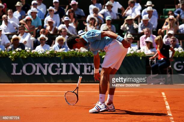 Novak Djokovic of Serbia smashes his racquet during his men's singles semifinal match against Ernests Gulbis of Latvia on day thirteen of the French...