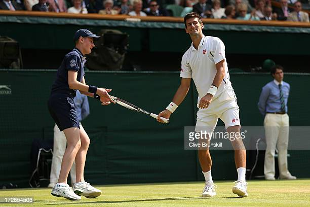 Novak Djokovic of Serbia smiles after falling on the grass as a ballboy hands him his racquet for him during the Gentlemen's Singles semifinal match...
