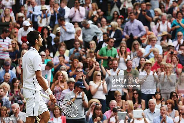 Novak Djokovic of Serbia stands dejected as the fans applaud during the Gentlemen's Singles Final match against Roger Federer of Switzerland on day...