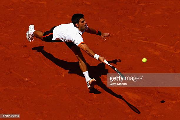 Novak Djokovic of Serbia stretches for a forehand in his Men's Singles match against Thanasi Kokkinakis of Australia on day seven of the 2015 French...