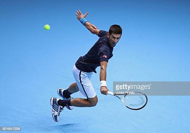 Novak Djokovic of Serbia stretches to hit a backhand during the Singles Final against Andy Murray of Great Britain at the O2 Arena on November 20...
