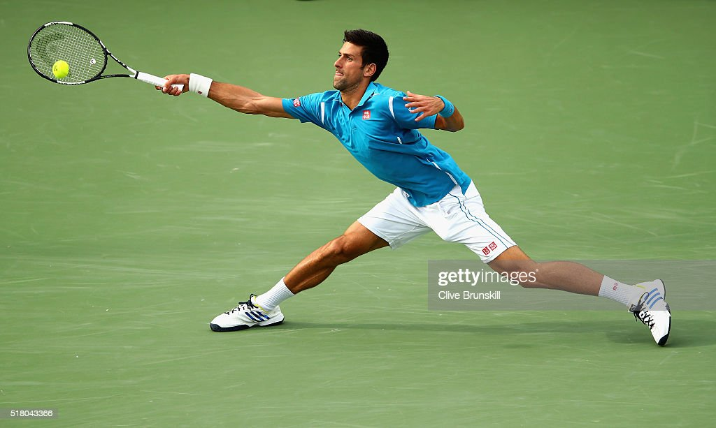 Novak Djokovic of Serbia stretches to play a forehand against Dominic Thiem of Austria in their fourth round match during the Miami Open Presented by Itau at Crandon Park Tennis Center on March 29, 2016 in Key Biscayne, Florida.