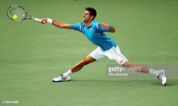 Novak Djokovic of Serbia stretches to play a forehand against Dominic Thiem of Austria in their fourth round match during the Miami Open Presented by...