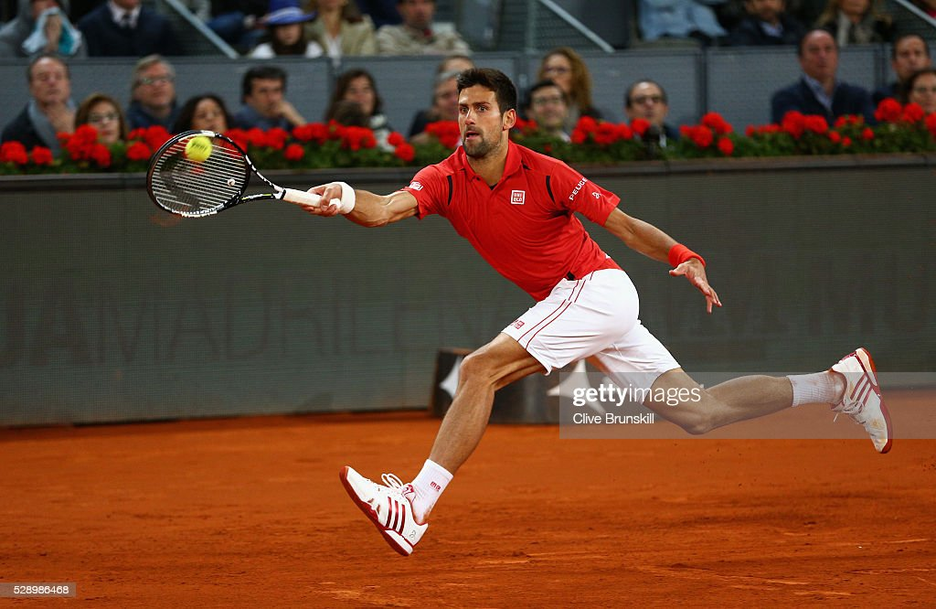 Novak Djokovic of Serbia stretches to play a forehand during his straight sets victory against Kei Nishikori of Japan in their semi final match during day eight of the Mutua Madrid Open tennis tournament at the Caja Magica on May 07, 2016 in Madrid,Spain.