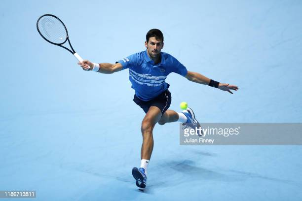 Novak Djokovic of Serbia stretches to play a forehand in his singles match against Matteo Berrettini of Italy during Day One of the Nitto ATP Finals...
