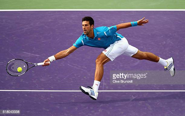 Novak Djokovic of Serbia stretches to play a forehand volley against Dominic Thiem of Austria in their fourth round match during the Miami Open...
