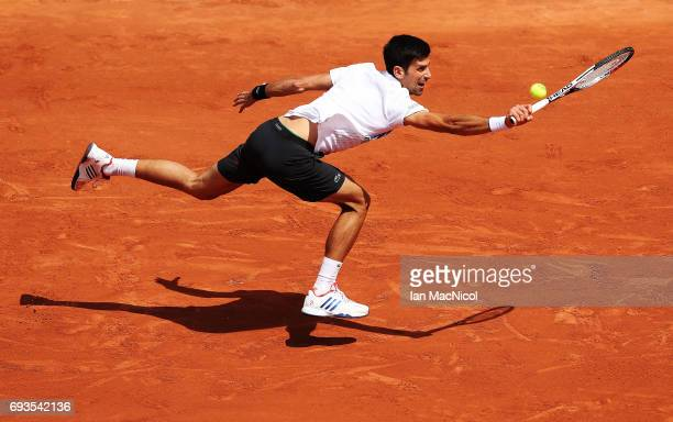 Novak Djokovic of Serbia stretches to play a shot during his match with Dominic Thiem of Austria, on day eleven at Roland Garros on June 7, 2017 in...