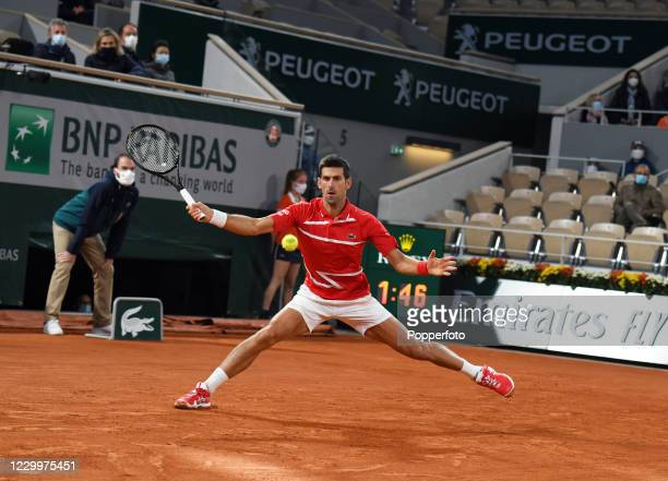 Novak Djokovic of Serbia stretches to return the ball against Rafael Nadal of Spain during the men's singles final on day fifteen of the 2020 French...